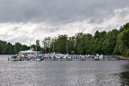 Mooring of yachts and boats on the lake in the city park in the Finnish town of Heinola.