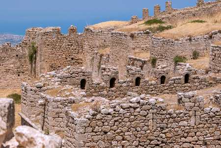 Ruined wall of ancient fortress Acrocorinth against the blue sky on a bright sunny day. Peloponnese, Greece.