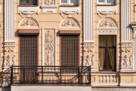 Windows with grilles, moldings and a balcony with a metal grating on the facade of the beige building. From the window series Saint-Petersburg.