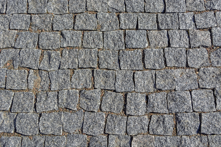 The image of a fragment of pavement from the gray paving stones to use as a background.