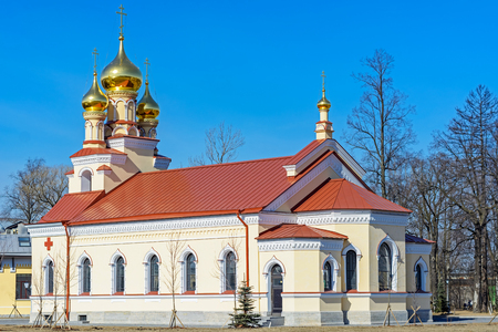 A small Orthodox church with golden domes and a red roof against the blue sky.