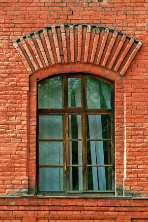 jalousie: Window with arch and lattice on the background of wall of red brick. From the series window of Saint-Petersburg.