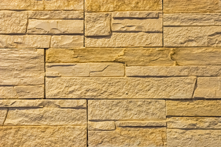 The wall is lined with beige rectangular tiles with a voluminous, rough surface. Stock Photo