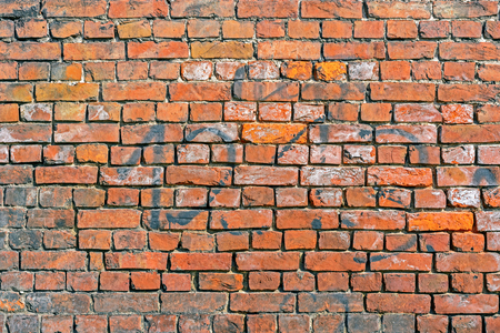 Fragment of a part of a wall of a house from an old red brick for use as a background. Stock Photo