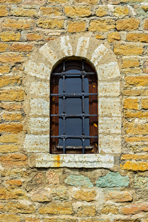 Window with an arch on the background of the wall of the old fortress of yellow limestone in the city of Narva. Stock Photo