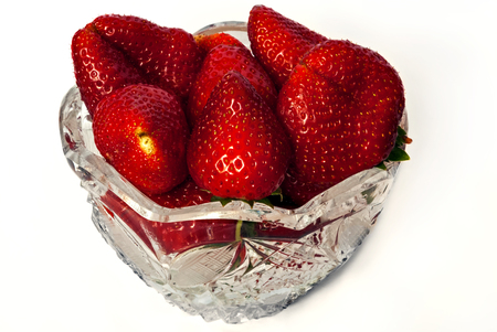 Berries of ripe, juicy, fresh, sweet, strawberries in a transparent crystal vase on a white background.