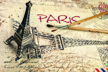 Notebook artist for sketches, with brushes for drawing and a statuette of the Eiffel Tower.