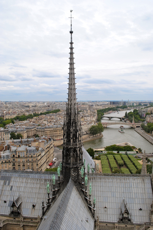Panorama of Paris overlooking the river Seine and the spire of Notre Dame Cathedral in the foreground against the sky.