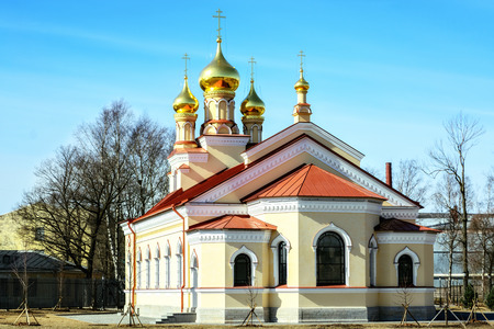 Small Orthodox church with gilded domes and a red roof against a blue sky.