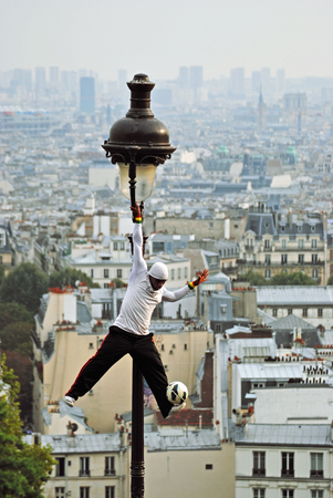 Paris, France, September 29: an Acrobat performs tricks with the ball, holding one hand over the top of a lamppost on the background of Paris roofs. Montmartre, 29 September 2013.