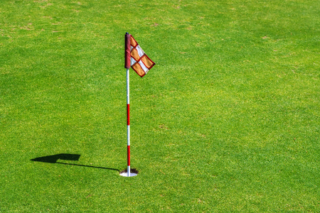Photo of a golf hole with a close-up flag in it, which casts a shadow on the green lawn of the field. Stock Photo