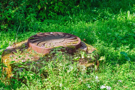 Cast iron cover on the manhole well sewer chamber among the green grass.