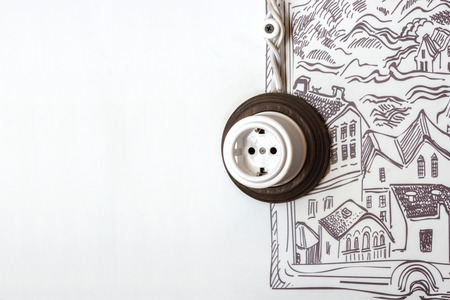 Household electrical socket with white woven wires against a white wall with a pattern.