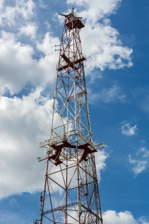 Fragment of the translation telephone tower against the blue sky with clouds. Stock Photo