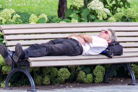 Budapest, Hungary, July 4: A man in a white shirt lay down to rest on a bench on the street of the city of Budapest on July 4, 2018.