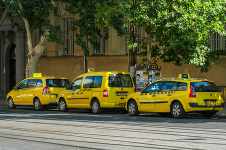 Budapest, Hungary, July 5: Three yellow taxis are waiting for their passengers on a street in Budapest on July 5, 2018.