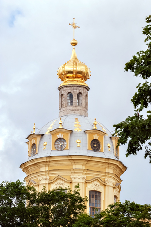 The tower of the church of yellow with a gilded dome and a cross against the background of a cloudy sky in the city of St. Petersburg.