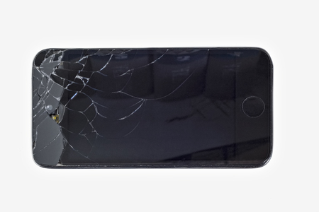 Smartphone black with  smashed shattered screen on a white background.