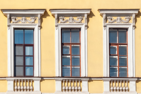 Three rectangular windows with a brown frame on the background of a yellow wall with a bas-relief. From a series of windows of St. Petersburg.