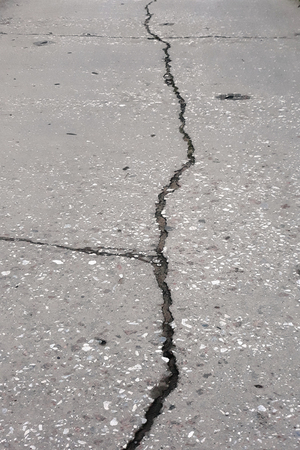 Crack in the concrete pavement of the road in the form of a broken line. Imagens