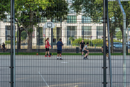 Budapest, Hungary, July 5: Young people playing basketball on a fenced urban sports ground in Budapest, July 5, 2018. Banque d'images - 117824041