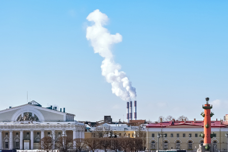 White smoke rising from the pipes of the city boiler room against the blue sky, with city buildings in the foreground. Banco de Imagens