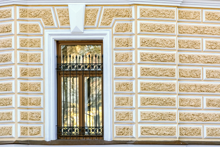 Corner rectangular window on the background of a yellow wall with stucco. From the window series of St. Petersburg.