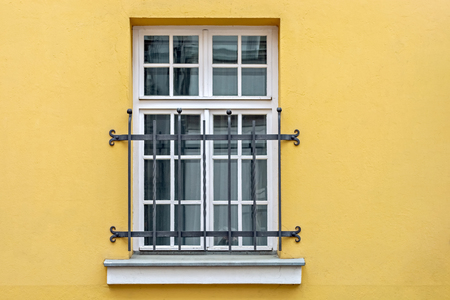 Window with a white rectangular frame and binding, located on the yellow wall of the house and closed decorative iron bars. From the series - Windows of the world.