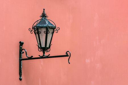 Street lamp on a black iron bracket on the background of a dark pink wall.