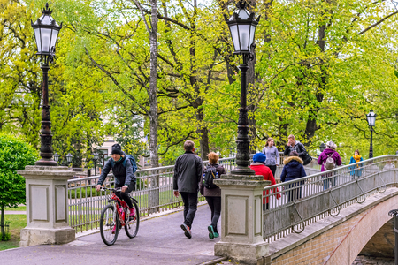 Riga, Latvia, may 02: Tourists and townspeople walk on the pedestrian bridge in the Park of the old part of Riga, may 02, 2019.