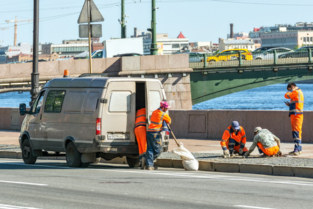 St. Petersburg, Russia, may 30: Five workers in orange overalls repairing cobblestone pavement on the Neva river embankment, may 30, 2019.