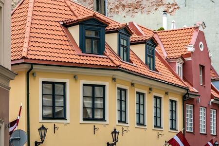 House with yellow walls, with attics on the roof of red tiles in the old part of Riga.