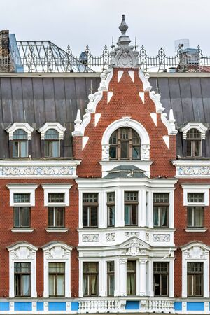 The facade of an old red brick building with white stucco windows and balconies in the old part of Riga.