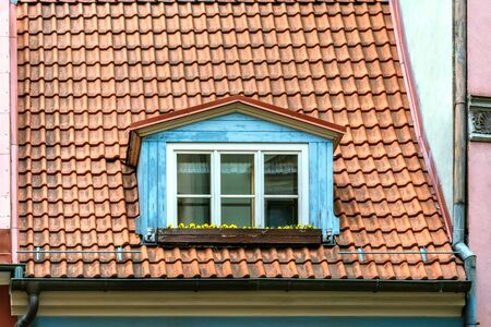 Attic window on the roof of red roof tiles in the old part of Riga. From the window series of the world. Imagens