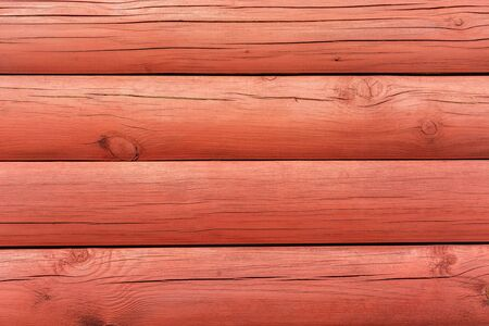 Fragment of a wall of logs painted in red color for use as an abstract background. 스톡 콘텐츠