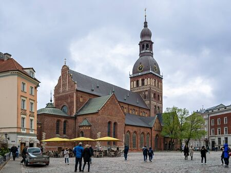 Riga, Latvia, may 02: Tourists walk on the dome square in front of the dome Cathedral in the old part of Riga, may 02, 2019. 新聞圖片