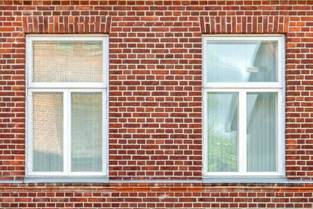 Two rectangular windows with white frames on a red brick wall background. From the window series of the world.