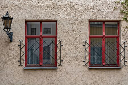 Two rectangular Windows with red frames against a pink wall and a city street lamp. From the window series of the world.