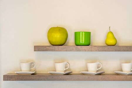 Interior with two shelves with white cups and fruit on beige wall background.