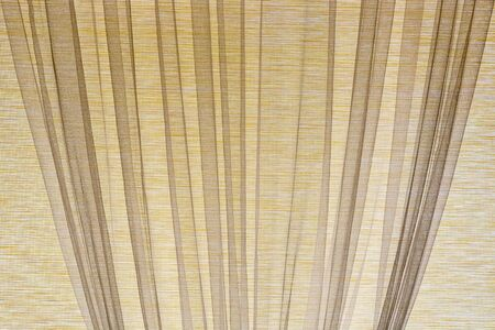 Curtains made of beige fabric on the window, for use as a texture and abstract background. 스톡 콘텐츠