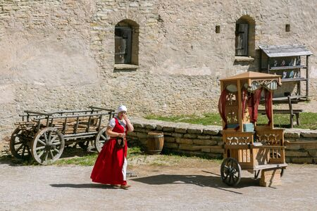 Rakvere, Estonia, June 28: View of the inner courtyard of the ancient castle in the city of Rakvere with a woman walking through it in a national red dress, on June 28, 2019. 에디토리얼