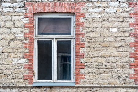 Rectangular window with a white wooden frame on the background of the old wall of stone and brick. From the window series of the world.