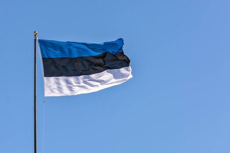 Estonian flag on the flagpole, waving in the wind against a blue sky.