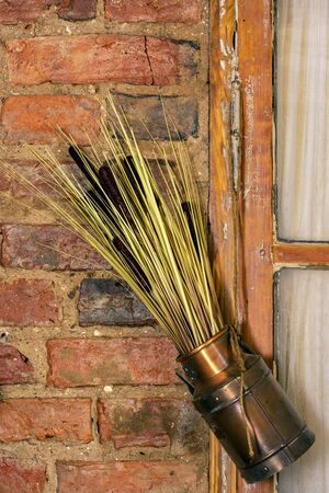 Ekibana from dried reeds in a copper pot on the background of a wall of red brick.