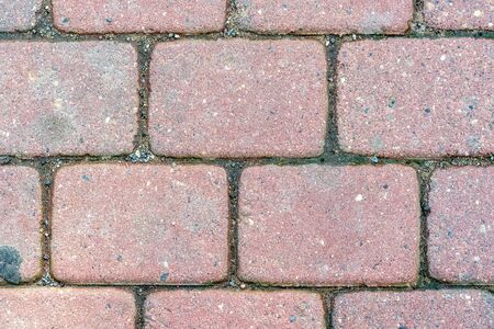 Fragment of the pavement, paved with stone blocks of pink color for use as an abstract background. Stockfoto - 129605042