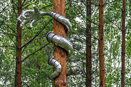 The snake is made in the form of an iron hand, twining the trunk of a pine.