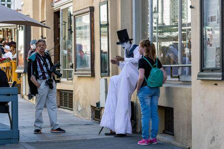 Tallinn, Estonia, June 28: Tourists lead a conversation with a street artist on Old Tallinn Street, June 28, 2019.