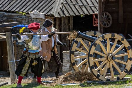 Rakvere, Estonia, June 28: A soldier loading an old cannon for a demonstration shot in the courtyard of the castle, June 28, 2019.