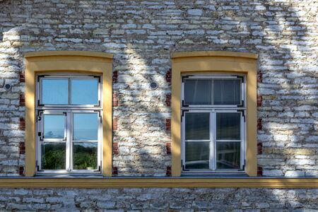 Two rectangular windows with yellow wooden frames on the background of a stone wall with a shadow from the tree. From the window series of the world.