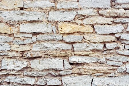 Fragment of an old stone wall made of limestone for use as an abstract background and texture.